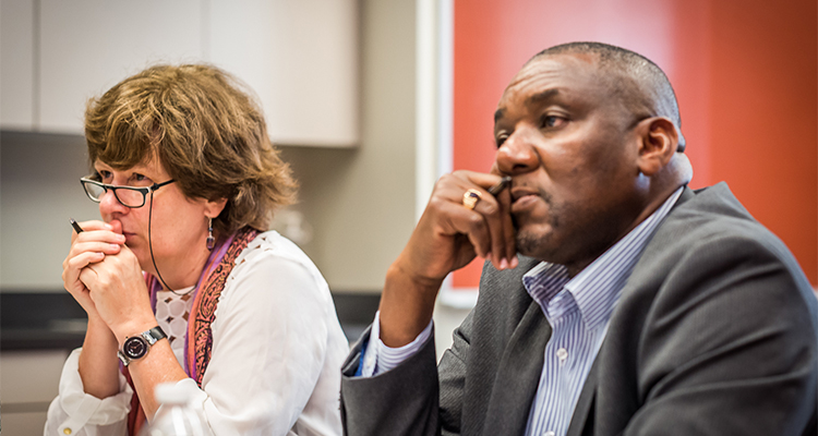 Black man and white woman pens in hand, listening intently