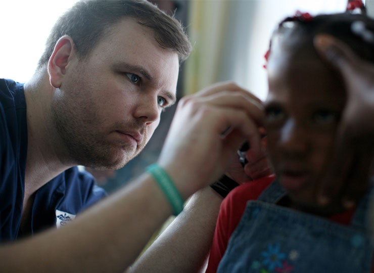 MD student inspects child's ear