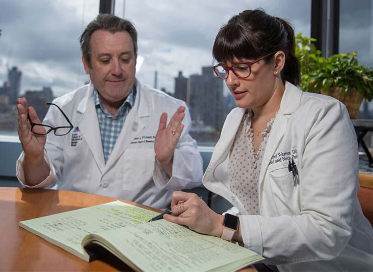 One doctor looking in book and another gesturing while speaking