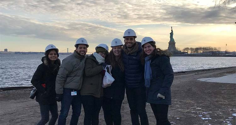 Students in hard hats with the statue of liberty in the background