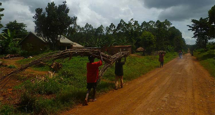 Dirt road with locals carrying bundles of wood