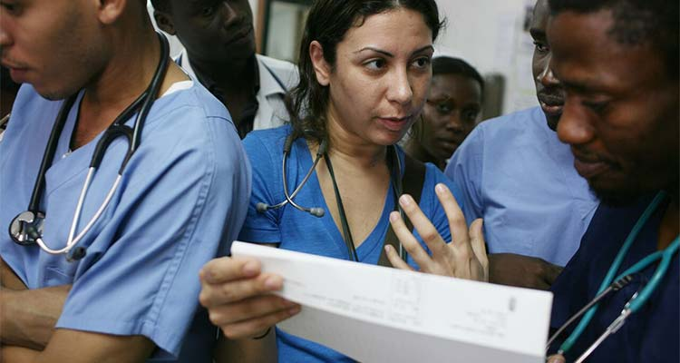Nurse holding paper and speaking to others