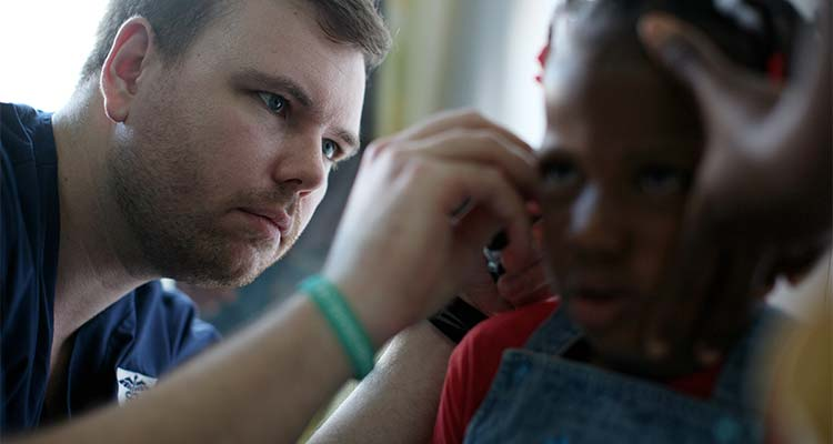 medical profesional checks child's ear