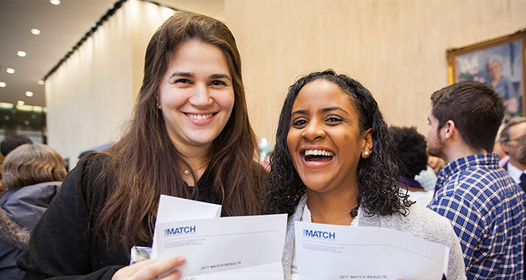2 Female medical students smile and share their Match day letters