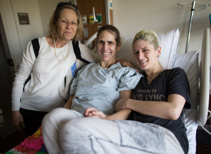 Two visitors posing with patient in hospital gown