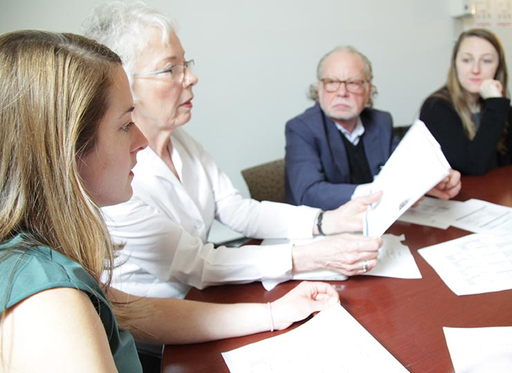 Four researchers sitting at a table reviewing information