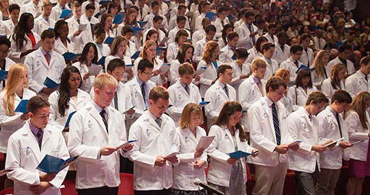 Students standing during white coat ceremony