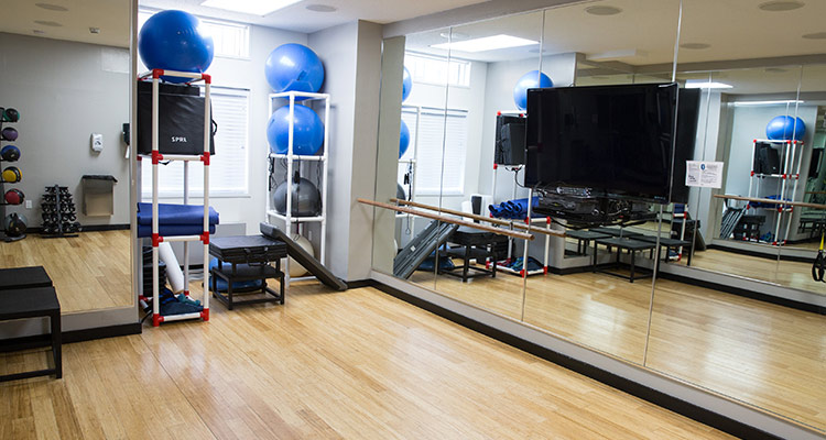 Fitness studio with wood floors, mirrors, and workout equipment