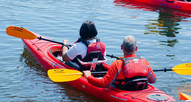 Man and woman in double red kayak